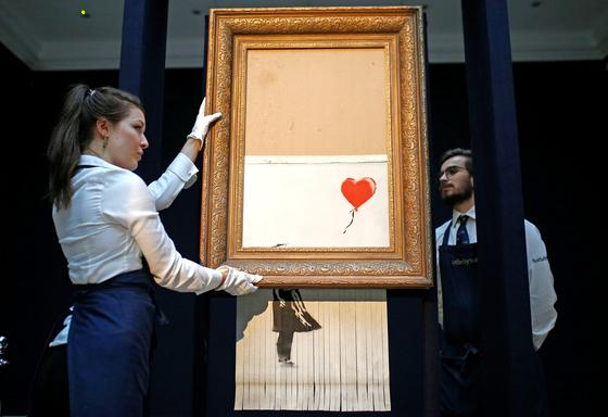 소더비 직원들이 12일 새롭게 탄생한 '쓰레기통 속의 사랑'을 공개하고 있다.[로이터=연합뉴스]