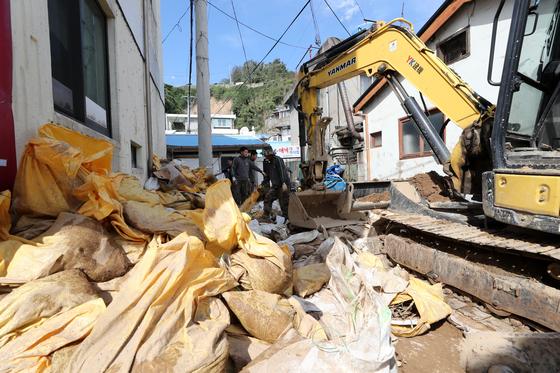 지난 10일 오후 경북 영덕군 강구면 대게 식당가에서 군인과 주민이 태풍 피해 복구에 나서고 있다. [연합뉴스]