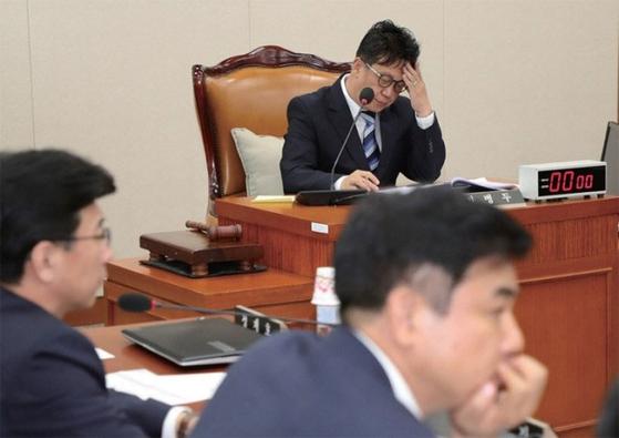 정무위원회 전체회의에서 국정감사 증인 채택을 놓고 여야 간 의견이 나뉘며 의원들의 발언이 이어지자 민병두 정무위원장이 생각에 잠겨 있다.