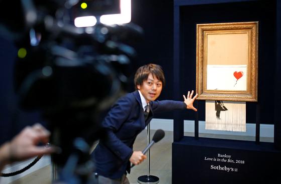 12일 런던 소더비에서 다시 공개된 뱅크시의 작품을 취재진들이 촬영하고 있다.[로이터=연합뉴스]