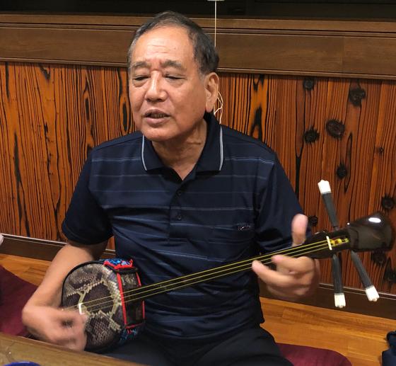 아마미오 섬 출신인 미나미 히로카즈(72) 씨가 전통악기인 쟈비센 반주에 맞춰 아마미 민요인 시마우타를 부르고 있다. 샤미센의 원조인 쟈비센은 샤미센보다 길고 통을 뱀가죽으로 덮은 것이 특징이다. 통을 덮는 가죽의 종류에 따라 소리가 달라진다고 한다. 사진=김상진 기자
