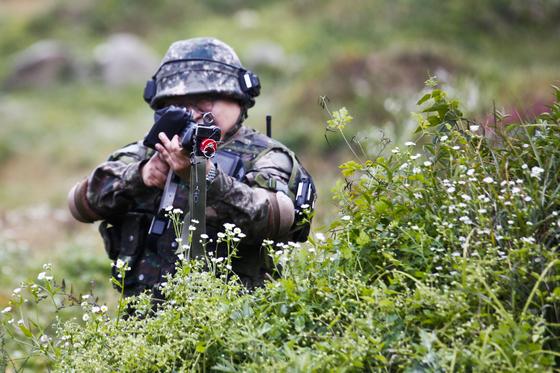 지난 11일 강원도 인제군 KCTC 훈련장에서 실전같은 모의 전투가 벌어졌다. 흙더미에 엄폐하던 기자가 대항군을 발견한 뒤 사격하고 있다. [사진 육군 제공]