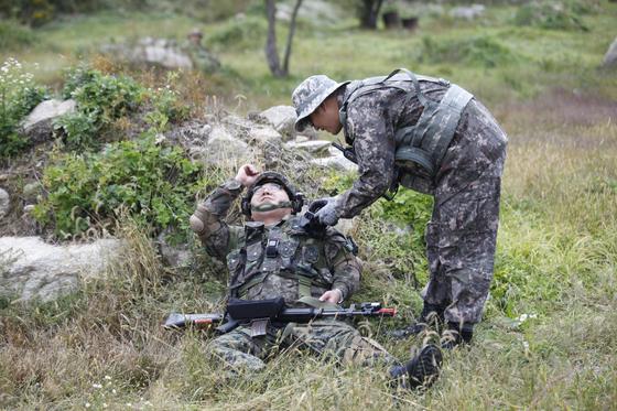 지난 11일 강원도 인제군 KCTC 훈련장에서 실전같은 모의 전투가 벌어졌다. 통제관이 마일즈 장비를 열어 전사를 확인하고 있다. 저 멀리 흙더미에 숨어있는 대항군이 보인다. [사진 육군 제공]