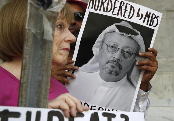 지난 10일(현지시간) 미국 워싱턴DC의 사우디아라비아 대사관 앞에서 시민들이 자말 카쇼기의 사진을 들고 항의하는 모습. [AP=연합뉴스]