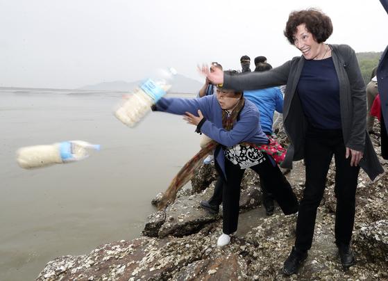 북한 인권운동가인 수잔 숄티 북한자유연합 대표가 지난 5월 강화도 해변가에서 쌀과 달러가 든 페트병을 바다로 던지고 있는 모습. [뉴시스]