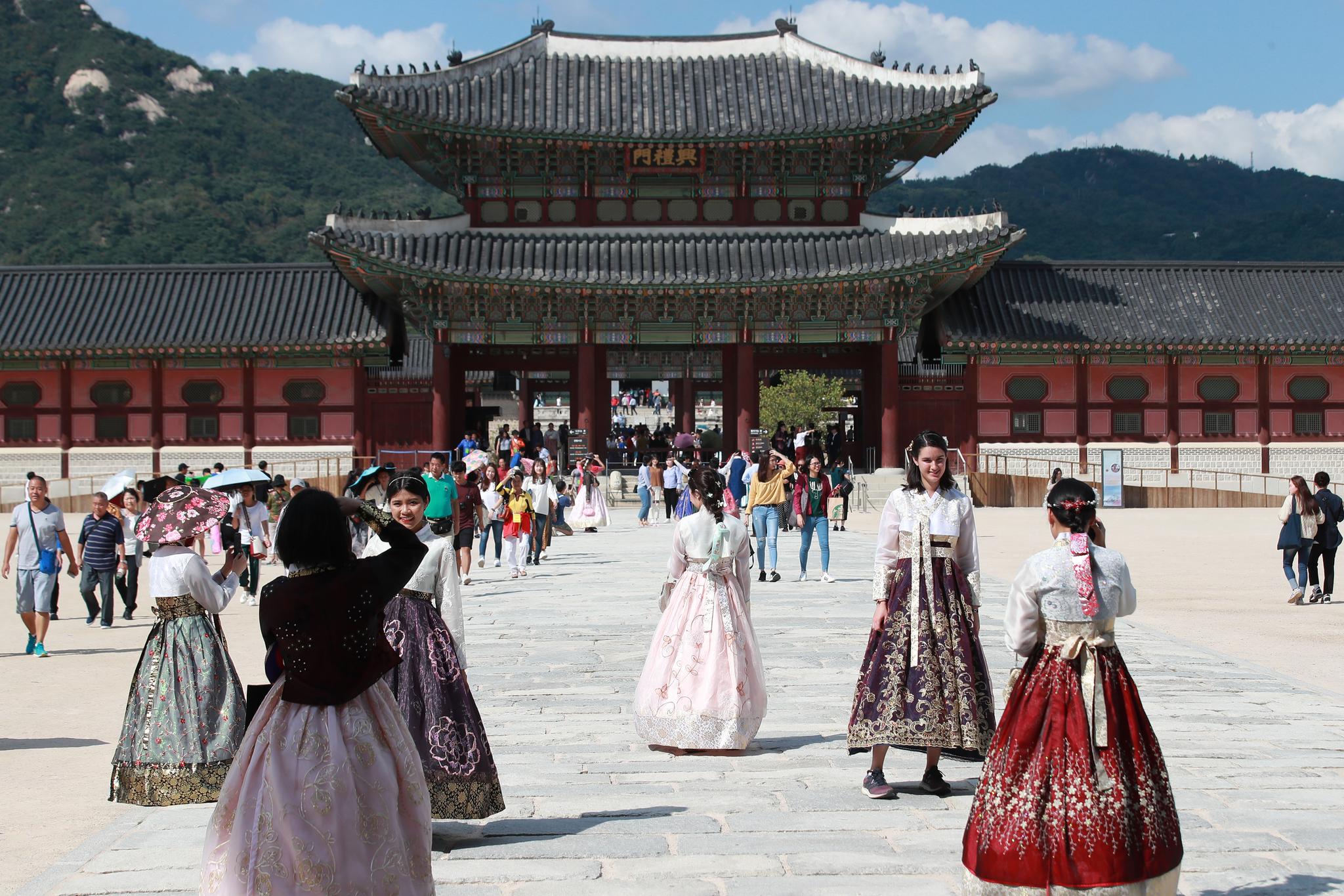지난달 12일 오후 서울 종로구 경복궁에서 '퓨전한복'을 입은 관광객들이 기념사진을 찍고 있다.   [연합뉴스]