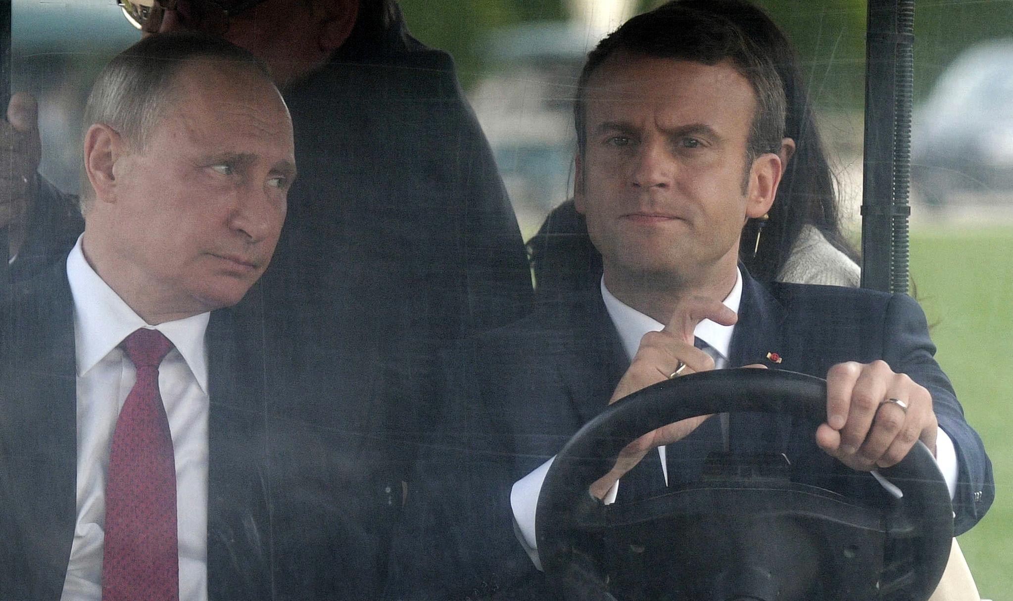 2017년 5월 프랑스 파리 인근 베르사유궁전에서 블라디미르 푸틴 러시아 대통령이 에마뉘엘 마크롱 프랑스 대통령과 함께 전기 골프카를 타고 있다. 푸틴 대통령이 운전하는 마크롱 대통령을 바라보고 있다. [AP=연합뉴스]
