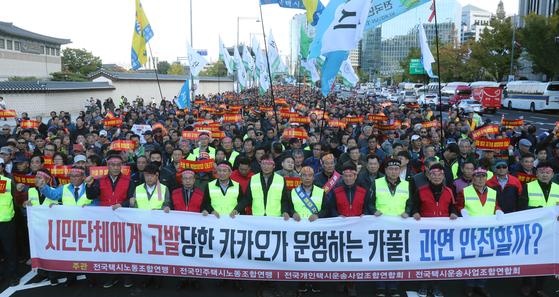 카카오가 도입한 카풀 서비스에 반대하는 택시업계 종사자들이 18일 오후 서울 광화문광장에서 생존권 사수결의대회를 열고 행진를 하고 있다. 강정현 기자