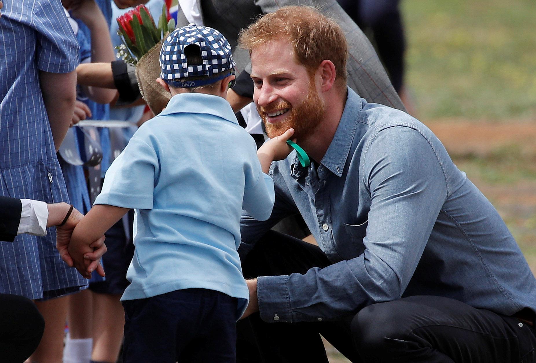 5살 루크 빈센트가 17일(현지시간) 호주 뉴사우스웨일스 주 더보 공항에서 환영나온 어린이들과 인사하는 영국 해리 왕자의 수염을 만지고 있다. [로이터=연합뉴스]