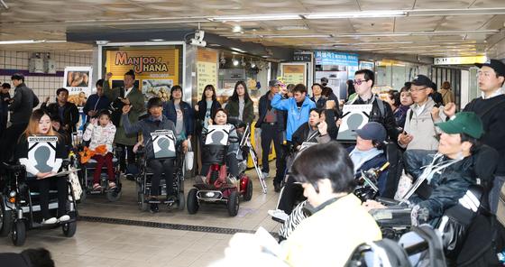 19일 서울 신길역 환승통로에서 열린 신길역 장애인리프트 추락사고 1주기 추모제에서 참석자들이 구호를 외치고 있다. [연합뉴스]