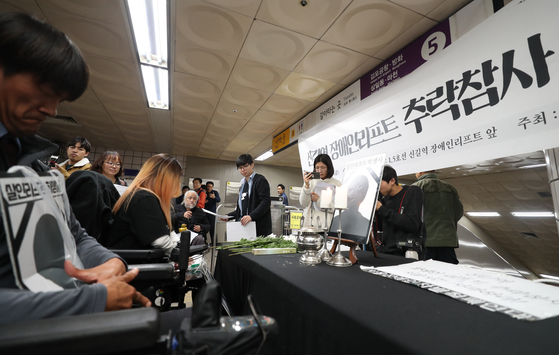 19일 서울 신길역 환승통로에서 열린 신길역 장애인리프트 추락사고 1주기 추모제에서 참석자들이 헌화하고 있다. [연합뉴스]