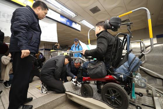 19일 서울 신길역 환승통로에서 열린 신길역 장애인리프트 추락사고 1주기 추모제를 찾은 장애인 참석자가 리프트 고장으로 내리지 못하고 있다. [연합뉴스]