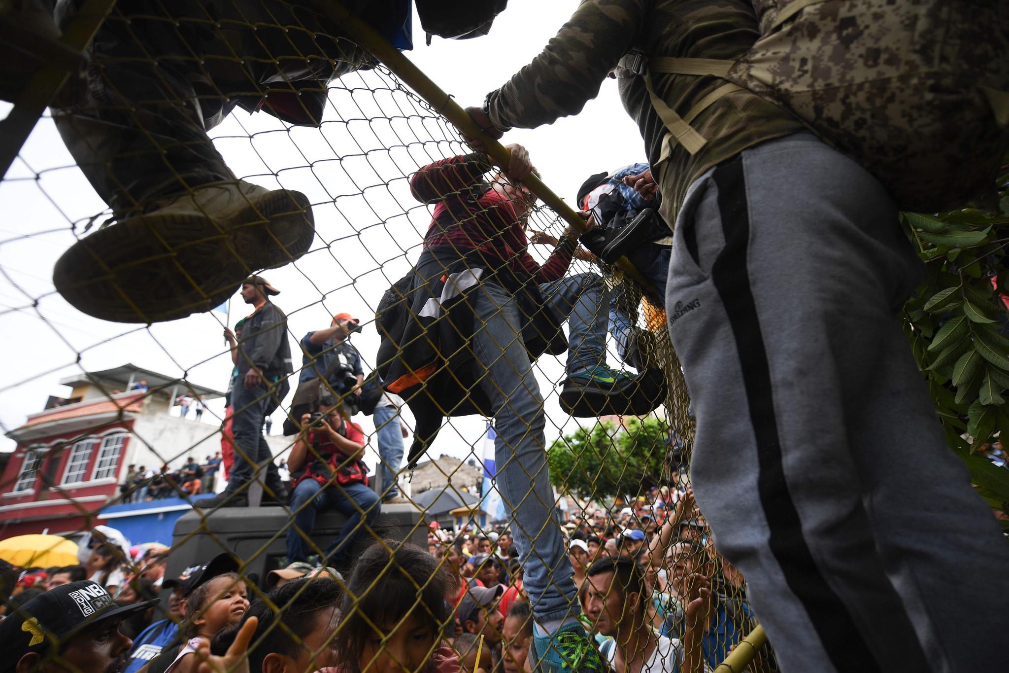 미국으로 향하는 온두라스 이주자들이 19일(현지시간) 과테말라와 멕시코 국경 다리로 가기위해 철문을 넘고 있다. [AFP=연합뉴스]