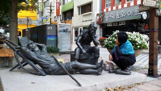 부산역에서 국제시장으로 걸어가다 보면 시장 상인의 피곤한 삶을 표현한 조형물이 많다. 지친 노동자의 모습에 마음이 짠해서 무언의 대화를 해봤다. [사진 송미옥]
