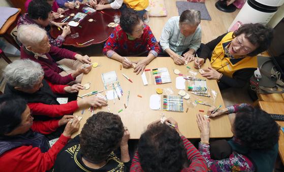 찾아가는 치매예방프로그램 '기억여행'에 참여한 할머니들이 열쇠고리에 색칠을 하고 있다. 강정현 기자