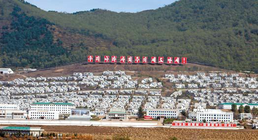 북한이 북·중 접경지역인 중강진 '3월5일청년광산' 인근에 조성한 대규모 주택단지. '우리나라 사회주의 제도 만세'란 선전 간판이 눈길을 끈다. [사진 통일문화연구소]