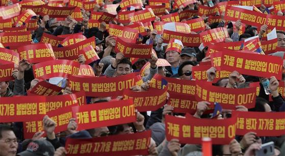카카오의 카풀 서비스에 반대하는 전국 택시 산업 종사자들이 10월 18일 서울 광화문광장에서 열린 '택시 생존권 사수 결의대회'에서 구호를 외치고 있다. / 사진:연합뉴스