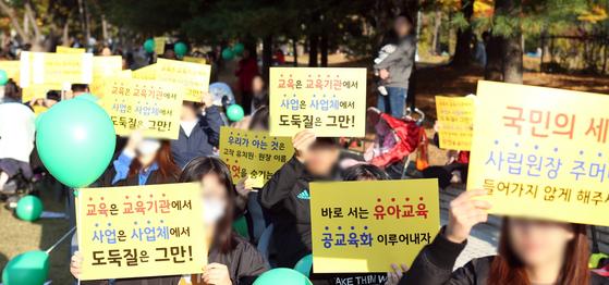 지난 21일 경기도 화성시 동탄신도시 센트럴파크에서 열린 사립유치원 비리 규탄 집회에서 학부모들이 피켓을 들고 있다. [사진=연합뉴스]