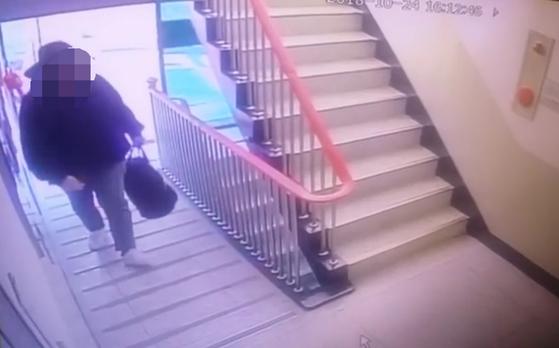 일가족 4명을 살해한 뒤 스스로 목숨을 끊은 것으로 의심받는 30대 남성이 24일 오후 범행장소인 부산 사하구의 한 아파트에 범행도구가 담긴 것으로 추정되는 가방을 들어 들어가는 장면이 아파트 CCTV에 잡혔다. [사진 부산경찰서]