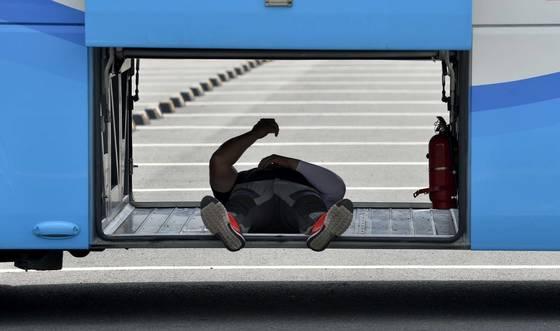 폭염주의보가 내려진 지난 7월 대전시 유성구 국립중앙과학관 주차장에서 마땅히 휴식장소를 찾지 못한 한 운전기사가 버스 짐칸에 들어가 휴식을 취하고 있다. [중앙포토]