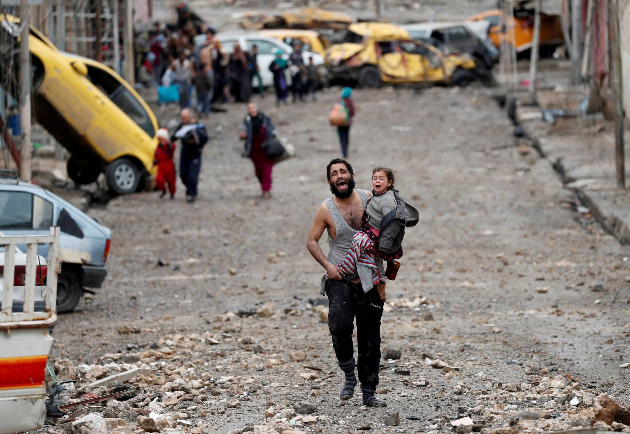 3월 4일. 이슬람 국가(IS)가 통제하던 이라크 모술 지역에서 폭격을 피해 딸을 안고 울면서 특수 부대에게 다가가는 남성. 그는 자살폭탄테러범이 아니라는 걸 증명하기 위해 셔츠를 들어올리라는 명령을 받았다. [REUTERS=연합뉴스/Goran Tomasevic]