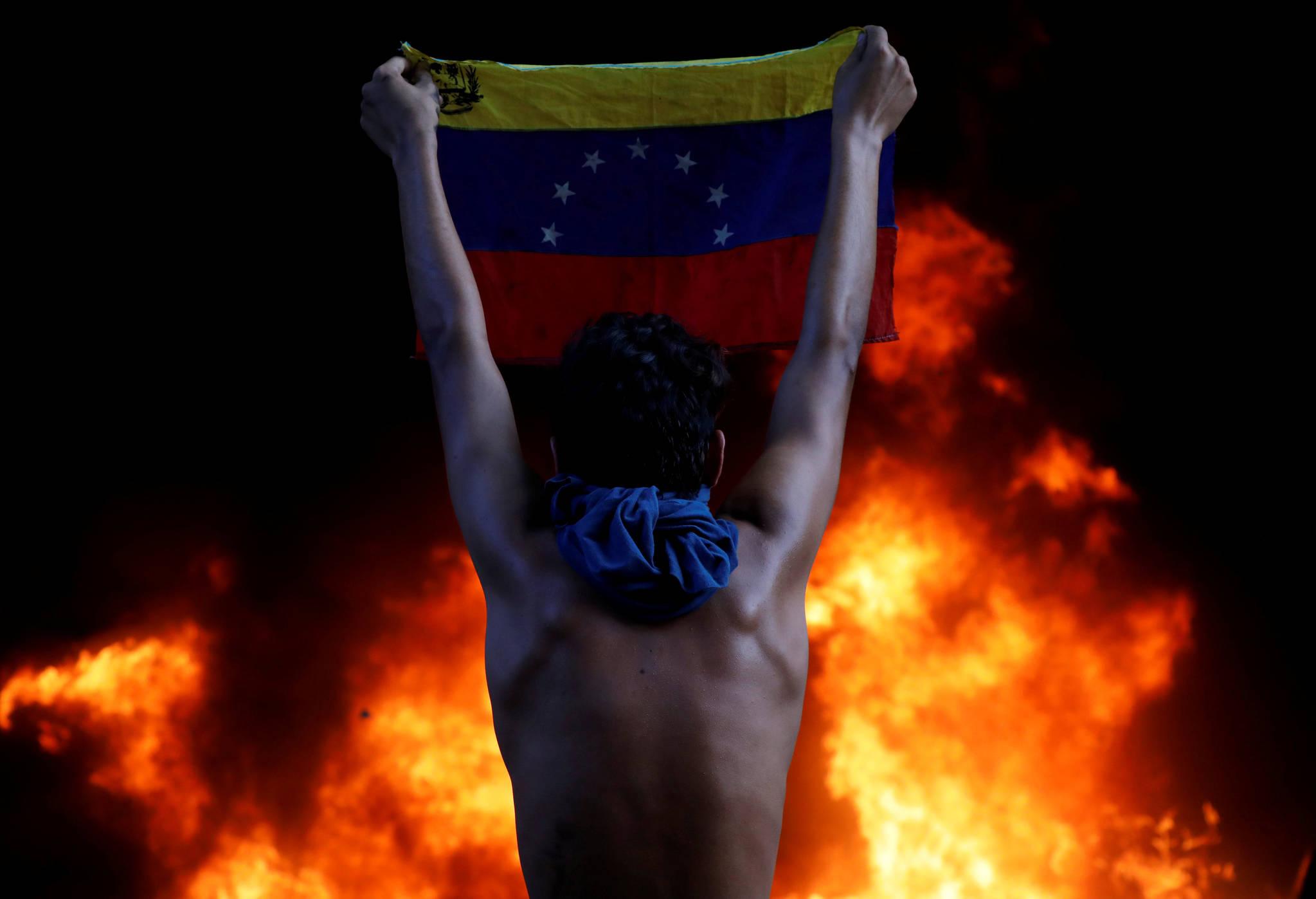 6월 12일. 베네수엘라 니콜라스 마두로 정권에 맞서 시위를 벌인 남성이 국기를 들고 있다. [REUTERS=연합뉴스/Carlos Garcia Rawlins]