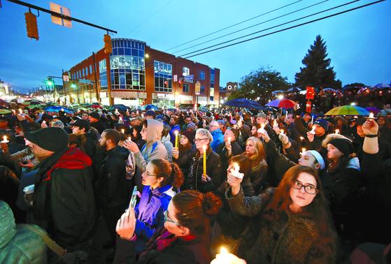 총기난사 사건이 발생한 미국 펜실베이니아주 피츠버그의 유대교 회당 '트리 오브 라이프' 인근에서 27일 주민들이 촛불을 들고 희생자들을 추모하고 있다. 이 날 유대인을 증오하는 40대 백인 남성 로버트 바우어스가 총을 난사해 11명이 숨지고 6명이 부상했다. [AP=연합뉴스]
