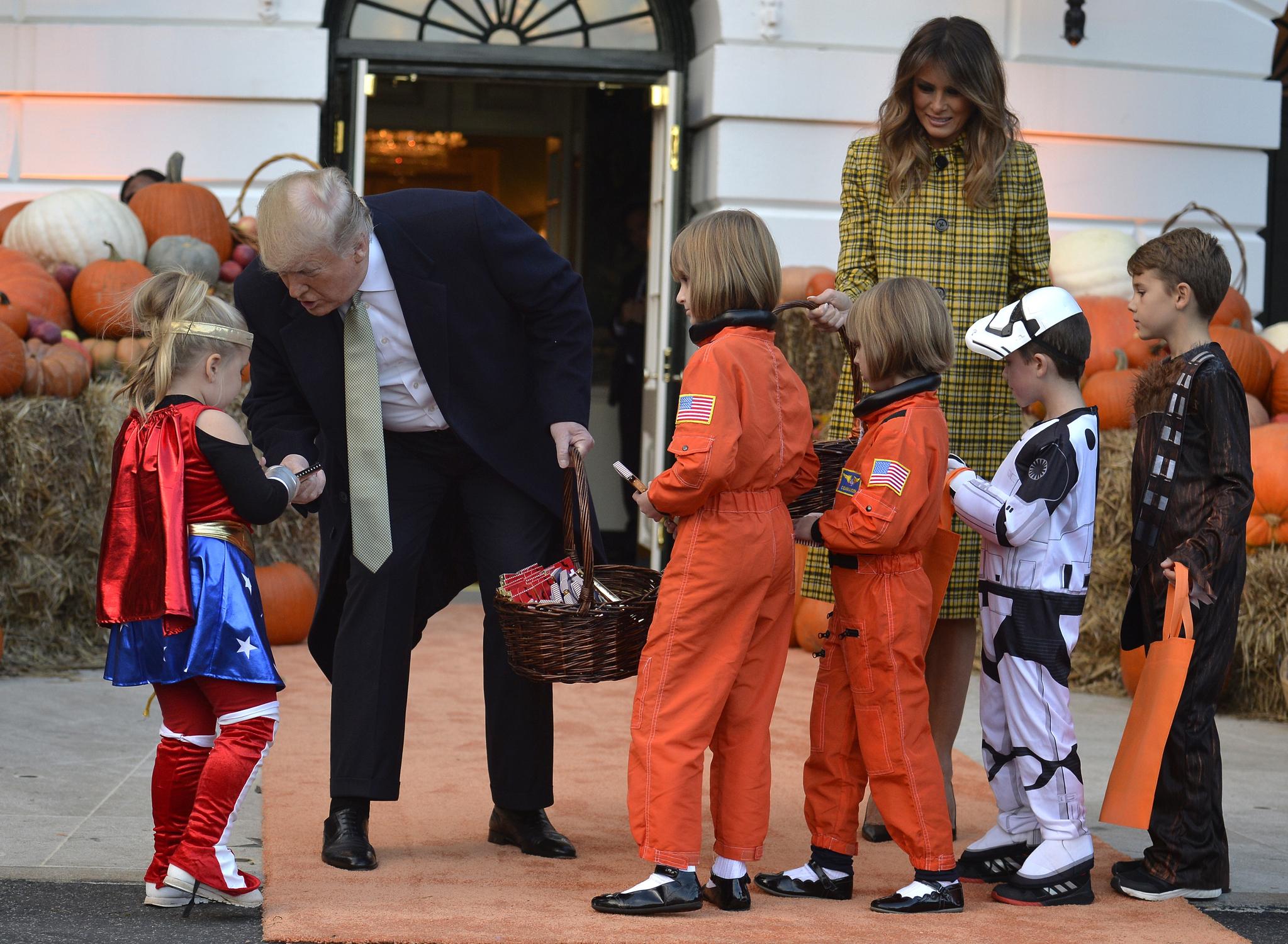 트럼프 대통령이 28일(현지시간) 백악관에서 열린 핼러윈 행사에서 슈퍼히어로 복장을 한 어린이에게 포장에 대통령 문양이 새겨진 사탕을 주고 있다. [EPA=연합뉴스]