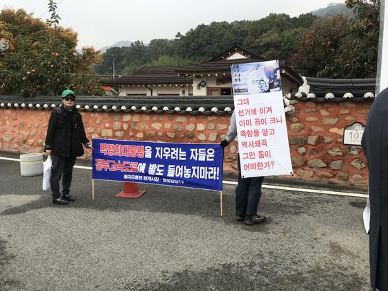 보수단체 회원들이 박정희 생가 앞에서 '박정희 지우기'에 반대하는 현수막을 들고 있다. 구미=김정석기자