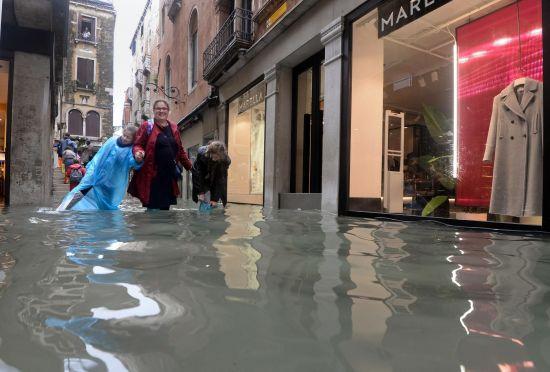 29일 침수 피해를 입은 베네치아 도심을 장화를 신고 걷고 있는 관광객들 [AP 뉴시스]