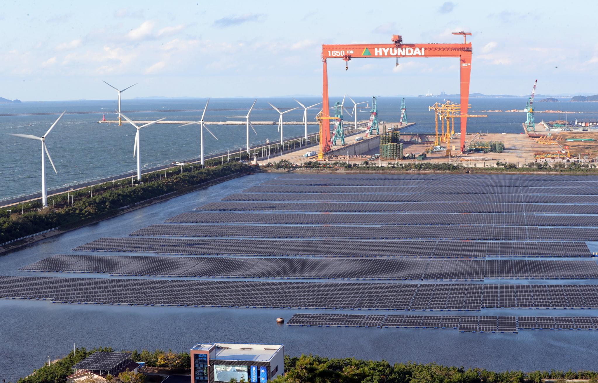 29일 오후 전북 군산시 군산2산업단지 유수지에 국내 최대 규모(유수지 면적 112,584평, 모듈 설치면적 67,548평)의 수상 태양광 발전소가 들어서 있다. 정부는 2022년까지 전북 새만금에 원자력 발전기 4기 용량에 해당하는 태양광 풍력발전단지를 건설할 계획이다. 뒷편은 가동이 중단된 현대중공업 군산조선소.[뉴스1]