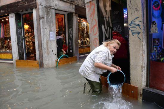 베네치아의 한 상점 주인이 건물에 범람한 물을 퍼내고 있다. [AP 뉴시스]