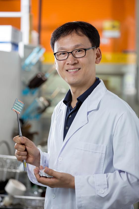 연구실에서 태양전지 재료를 들고 있는 김진영 교수.[사진 UNIST]