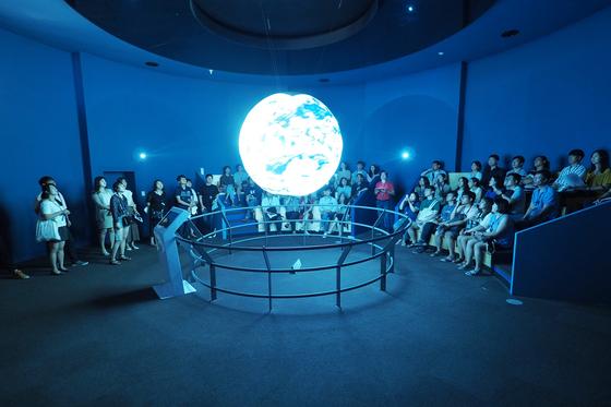지난 8월 국립과천과학관이 주최하는 '달밤 과학파티' 참여자들이 자연사관에 있는 SOS(Science on Sphere)을 감상하고 있다. 파티는 만 19세 이상 성인만 참여할 수 있다. [사진 국립과천과학관]