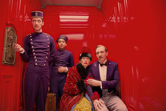 '그랜드 부다페스트 호텔'의 엘리베이터 안이다. (오른쪽부터) 호텔 지배인 구스타브와 세계 최고 부호 마담 D., 로비 보이 제로. 엘리베이터의 색과 호텔 직원들의 유니폼, 마담 D.의 옷까지 색감이 화려하다.