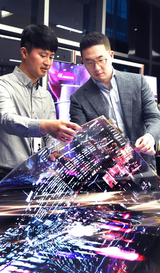 구광모 LG그룹 회장(오른쪽)이 지난 9월 서울 강서구 마곡 LG사이언스파크에서 LG디스플레이 연구원과 함게 '투명 플렉시블 OLED'를 살펴보고 있다. [사진 LG그룹]