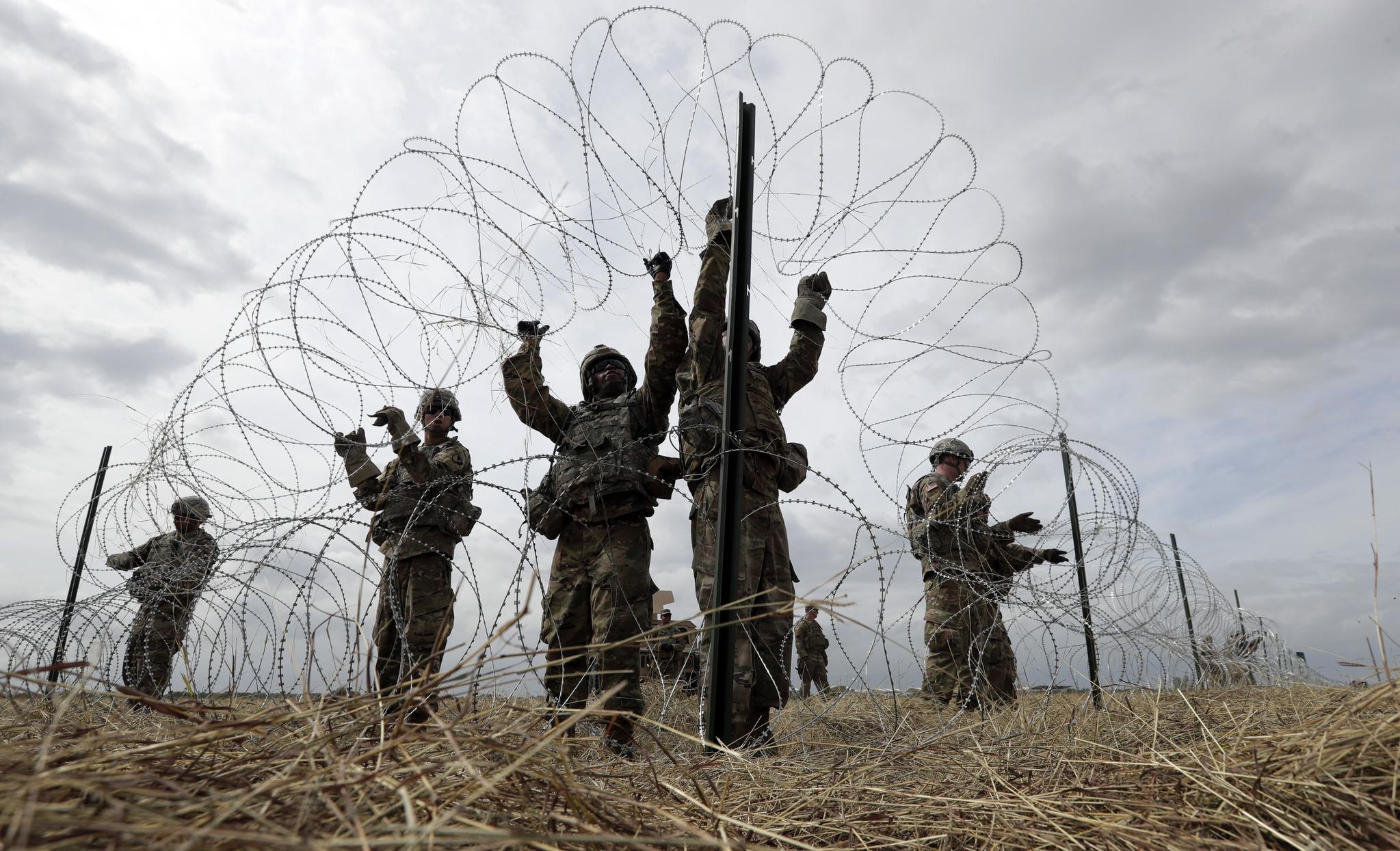 미군이 4일(현지시간) 미국-멕시코 국경 인근인 텍사스 도나에서 국방부와 세관 국경 보호국을 위한 캠프 주변에 가시 철조망을 설치하고 있다. [AP=연합뉴스]