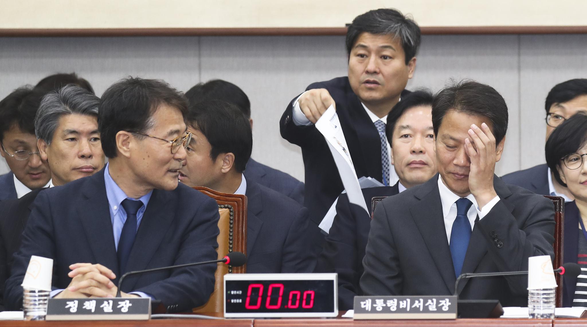 임종석 청와대 비서실장(오른쪽)이 6일 국회에서 열린 국회 운영위원회의 청와대에 대한 국정감사에서 장하성 정책실장과 대화하며 얼굴을 만지고 있다. 임현동 기자