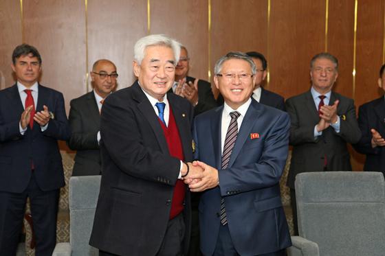 평양에서 만나 손을 맞잡은 조정원(왼쪽) WT 총재와 리용선 ITF 총재. [뉴스1]