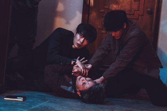 '손 the guest'에서 구마 사제 역할을 맡은 김재욱과 구마의식을 행하고 있는 모습. [사진 OCN]