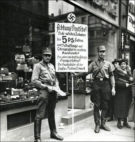 수정의밤 다음날 함부르크의 유대인 소유 상점 앞을 나치 돌격대원들이 지키고 있다. 들고 있는 피켓에는 유대인 상점 주인이 독일 직원에게 굶어죽을 정도의저임금만 줬다고 니난하는 내용이 적혀 있다. [독일 연방 문서보관소]