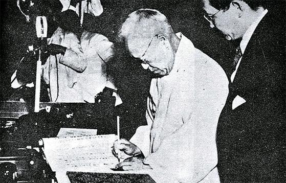 1948년 7월 17일 이승만 초대 국회의장의 제헌국회가 제정한 헌법에 서명하고 있다. [중앙포토]