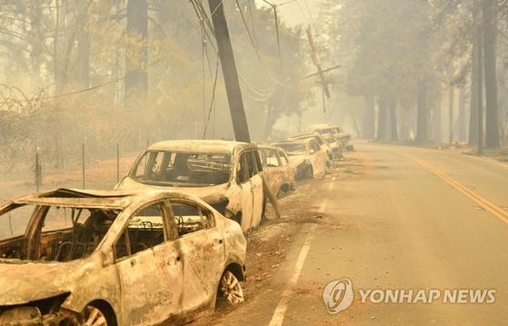 대형산불이 발생한 미국 캘리포니아주 북부 뷰트카운티의 파라다이스 지역에서 9일(현지시간) 버려진 차량들이 불에 탄 채 도로에 줄지어 세워져 있다. 샌프란시스코에서 북동쪽으로 290㎞ 떨어진 뷰트카운티에서 발화한 대형산불 '캠프파이어'가 카운티 내 파라다이스 마을을 통째로 집어삼켰다. [AFP=연합뉴스]