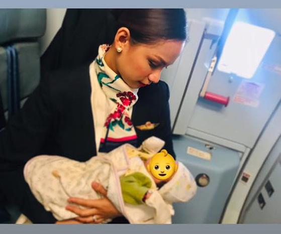 기내에서 승객의 아이를 안고 있는 패트리샤 오르가노 [패트리샤 페이스북 캡처]