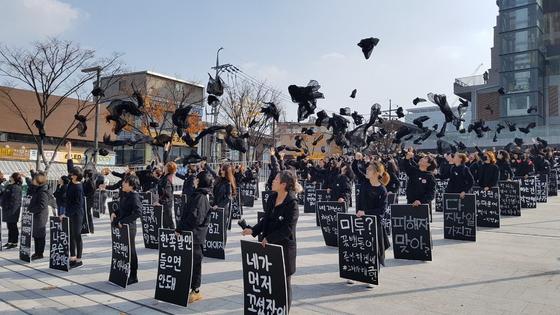 10일 다시세운광장에 모인 참가자들이 얼굴에 둘렀던 검은 천을 위로 던지고 있다. [사진 #미투 운동과 함께하는 시민행동]