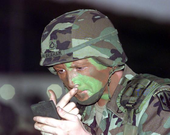 미 육군 병사가 안면크림을 바르고 있다. 이 병사가 입은 전투복이  BDU다. [사진 미 육군]