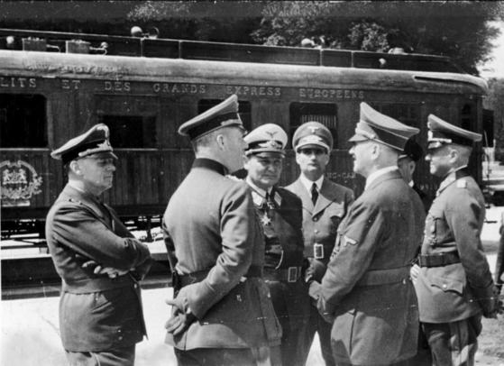 1940년 프랑스를 점령한 나치 독일은 1차대전 전전협정을 서명했던 포슈 전용 기차를 서명 장소인 콩피에뉴로 가져와 6월 22일 프랑스의 항복을 받았다. 바로 그 기차 앞에서 환담을 나누는 아돌프 히틀러(오른쪽에서 둘째)와 그 일행. [위키피디아]