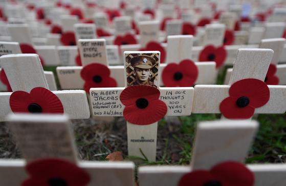 제1차 세계대전 종전 100주년을 맞는 11월 11일을 앞둔 지난 6일 영국 런던 웨스트민스터 사원의 '추모의 뜰'에 전몰자를 기리는 포피 조화가 줄줄이 꽂혀 있다. 개양귀비꽃인 포피는 1차대전 당시 서부전선의 주전장인 플랑드르 전선의 들판에 많이 피었던 꽃으로 추모의 상징이 됐다. 영국과 영연방 국민의 상당수는 종전기념일을 전후해 가슴에 포피 조화를 달고 다닌다. 전쟁 당시 젊은 세대의 40%가 숨진 참극을 기억하자는 의미다. [EPA=연합뉴스]