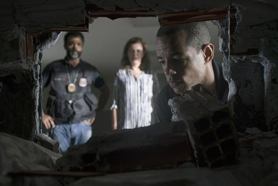 드라마 '부패의 메커니즘'의 한 장면. 벽 안에 숨겨진 돈다발을 들여다보는 경찰.