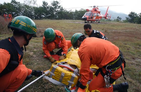 조난자를 들것에 실어 헬기로 후송하는 훈련을 하는 소방 구조대원들의 모습. 사진은 기사와 관련 없음. [중앙포토]
